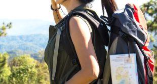 Frau bei Wanderung in der Natur schaut durch Accu Buddy