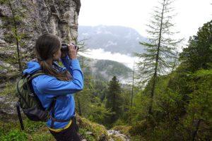 Frau in den Bergen schaut durch Steiner Fernglas Ultra Sharp