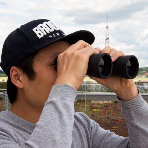 Mann schaut durch TS-Optics 16x50 Fernglas