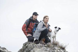 Frau, Mann und Hund auf Berg mit Steiner Fernglas